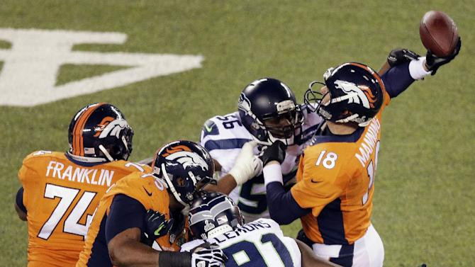 In this Feb. 2, 2014, file photo, Denver Broncos' Peyton Manning is hit by Seattle Seahawks' Cliff Avril (56) during the first half of the NFL Super Bowl XLVIII football game in East Rutherford, N.J. One of the hallmarks of the Seahawks' Super Bowl run was the ability to wreak havoc on quarterbacks but this season Seattle's pass rush is not close to matching its effectiveness from last year