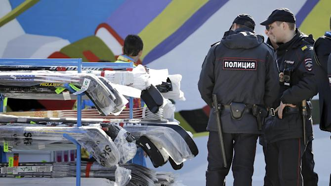 Police officers look over a cart of hockey sticks after they were taken off a plane as NHL hockey players arrive at the Sochi International Airport for the 2014 Winter Olympics, Monday, Feb. 10, 2014, in Sochi, Russia