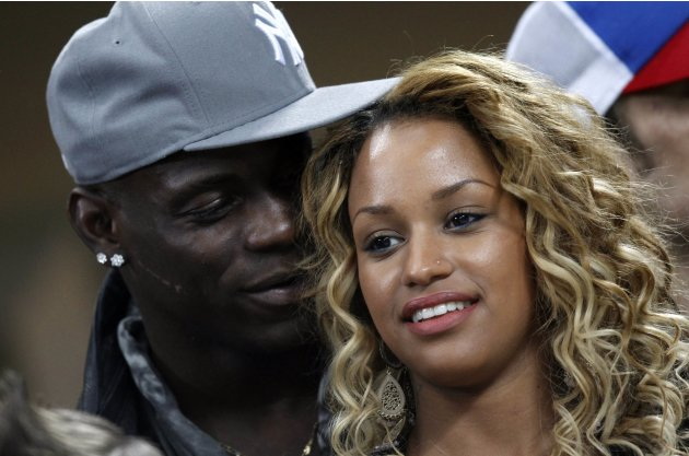 AC Milan's Balotelli talks with his girlfriend, model Fanny Robert Neguesha, as they watch their Champions League soccer match against Barcelona at the San Siro stadium in Milan