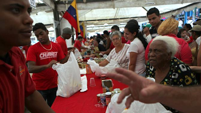 Residents buy subsidized food at a government market in Caracas, Venezuela, Saturday, Oct. 6, 2012. President Hugo Chavez is running for re-election against opposition candidate Henrique Capriles in Sunday's presidential election. (AP Photo/Rodrigo Abd)