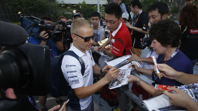 Williams Formula One driver Bottas of Finland signs autographs as he arrives for the first practice session of the Singapore F1 Grand Prix at the Marina Bay street circuit in Singapore