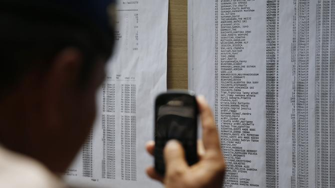 A man takes a picture of the list of passengers onboard AirAsia flight QZ8501 at Juanda International Airport in Surabaya