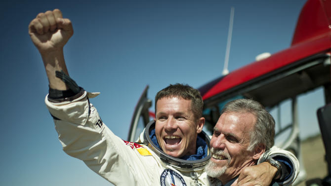 In this photo provided by Red Bull Stratos, pilot Felix Baumgartner of Austria and Technical Project Director Art Thompson, celebrate after successfully completing the final manned flight for Red Bull Stratos in Roswell, N.M., Sunday, October 14, 2012.Baumgartner came down safely in the eastern New Mexico desert minutes about nine minutes after jumping from his capsule 128,097 feet, or roughly 24 miles, above Earth. (AP Photo/Red Bull Stratos, Joerg Mitter)