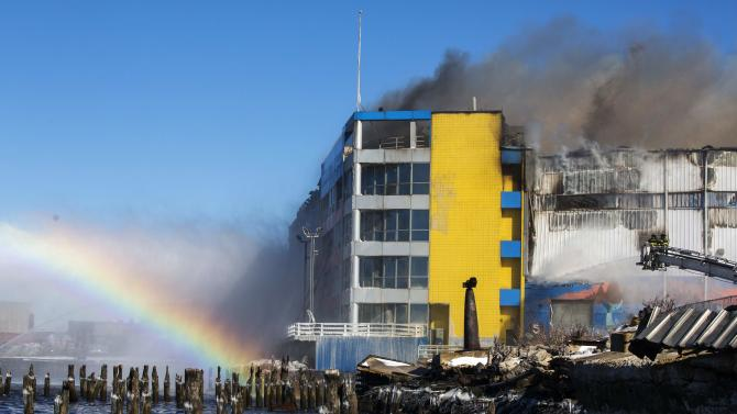 Members of the New York Fire Department battle a six alarm fire in a storage facility on the waterfront of the East River in New York