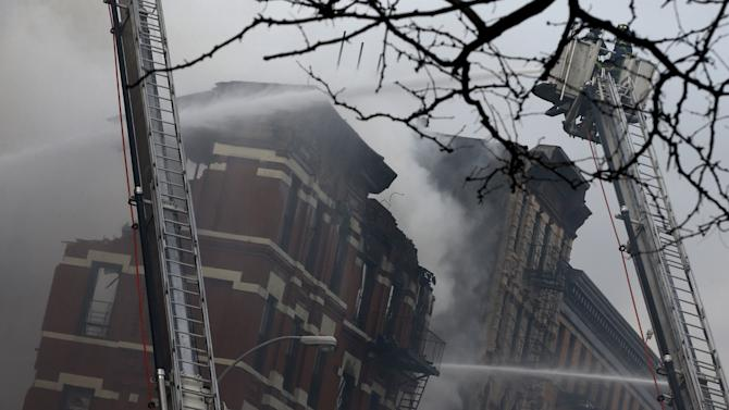 Firefighters battle a fire at the site of a residential apartment building collapse and fire in New York City's East Village neighborhood