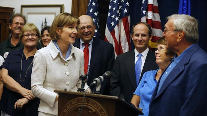 Attorney General Lori Swanson, foreground left, thanks Don Williams, right, and his wife for their courageous testimony in the Accretive Health Inc. case Monday, July 30, 2012 in St. Paul, Minn. Swanson announced a legal settlement Monday that will bar Chicago-based Accretive Health Inc. from doing business in Minnesota for six years after she accused the medical revenue company of intrusive efforts to collect money from patients in several hospitals. (AP Photo/The Star Tribune, Richard Tsong-Taatarii)  MANDATORY CREDIT; ST. PAUL PIONEER PRESS OUT; MAGS OUT; TWIN CITIES TV OUT