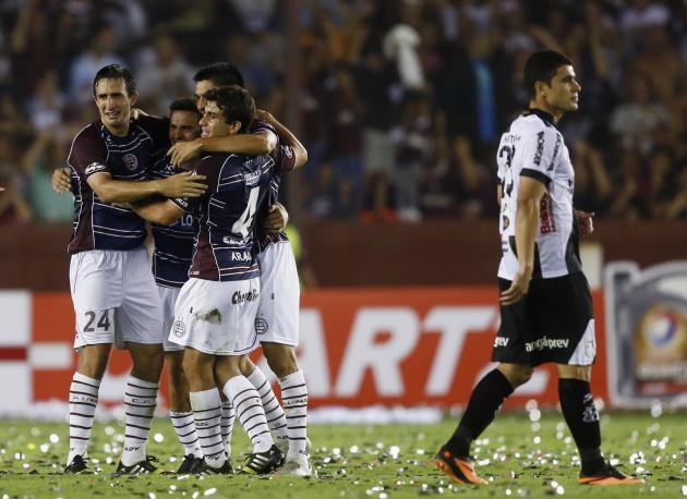 Players of Argentina's Lanus celebrate as Silva of Brazil's Ponte Preta walks past at end of Copa Sudamericana final soccer match in Buenos Aires