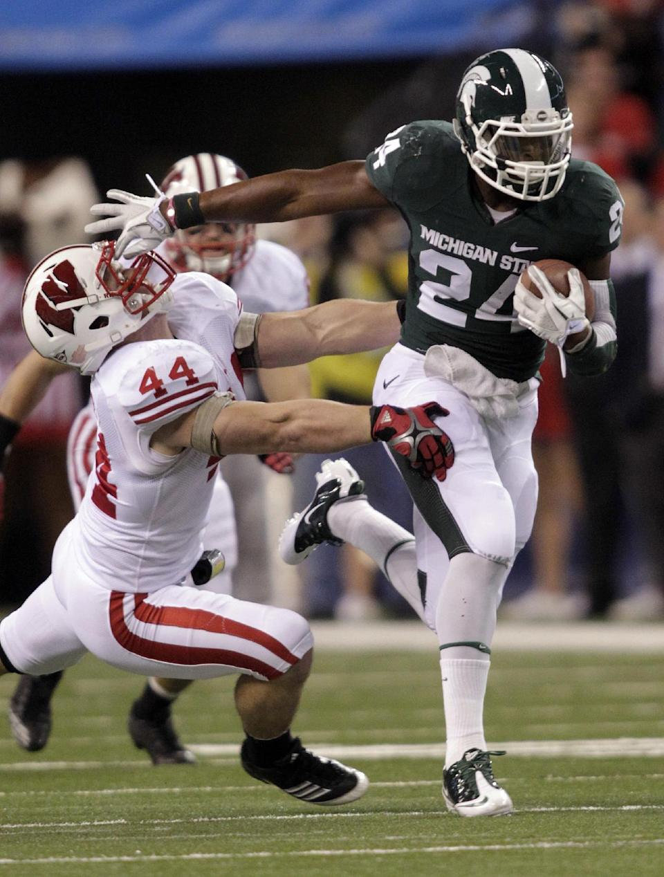 Michigan State's Le'Veon Bell runs out of the tackle of Wisconsin's Chris Borland during the first half of the Big Ten conference championship NCAA college football game, Saturday, Dec. 3, 2011, in Indianapolis.  (AP Photo/AJ Mast)
