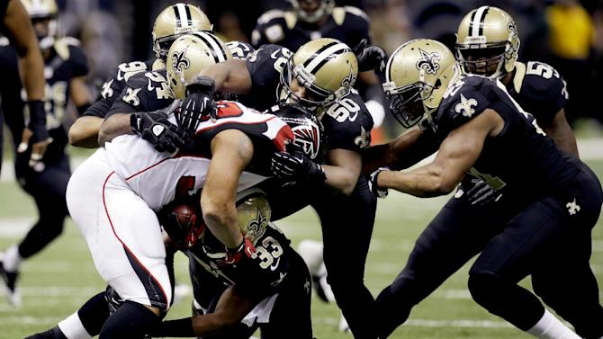 Atlanta Falcons running back Michael Turner (33) is stopped by New Orleans Saints middle linebacker Curtis Lofton (50), cornerback Jabari Greer (33), defensive end Cameron Jordan (94) and outside linebacker Jonathan Vilma (51) in the second half of an NFL football game at Mercedes-Benz Superdome in New Orleans, Sunday, Nov. 11, 2012. (AP Photo/Bill Haber)