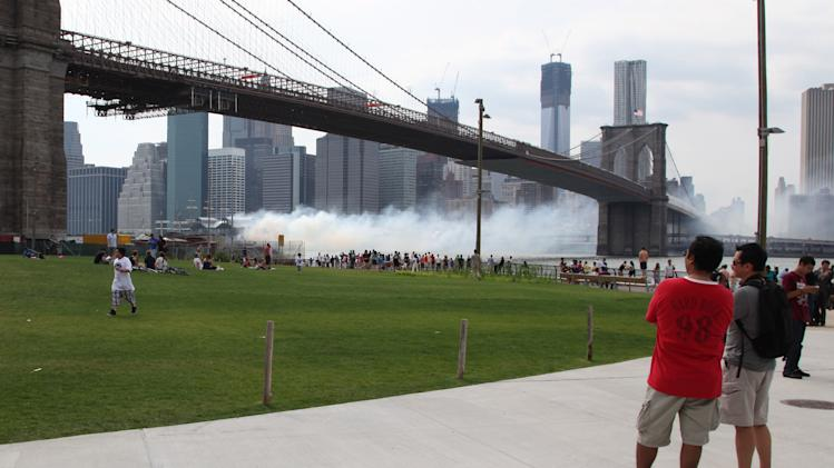 Spectators in the Brooklyn borough of New York watch a smoky fire on the opposite side of the Brooklyn Bridge as firefighters battle a three alarm blaze at the South Street Seaport, Saturday, July 14, 2012 in New York. About 140 firefighters and the U.S. Coast Guard responded to the blaze that broke out about 4 p.m. Saturday. There were no injuries. (AP Photo/Lisa Tolin)