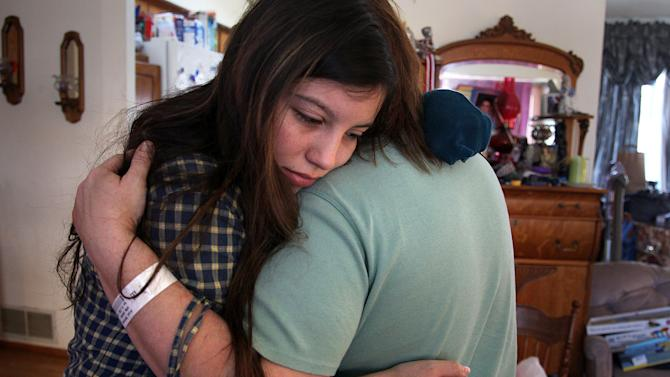 Savannah Laventure, 18, the sister of shooting victim 9-year-old Devin Aryal, comforted their mother Melissa Aryal , at their home, Tuesday, Feb. 12, 2013 in Oakdale, Minn. Police were still trying to determine Tuesday why a 34-year-old man randomly shot at passing vehicles in a suburban St. Paul neighborhood, wounding Melissa Aryal and killing her son Devin, an aspiring astronaut whom she'd just picked up from daycare. (AP Photo/The Star Tribune, Elizabeth Flores)