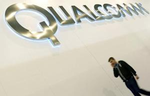A man walks past a Qualcomm advertising logo at the Mobile World Congress at Barcelona