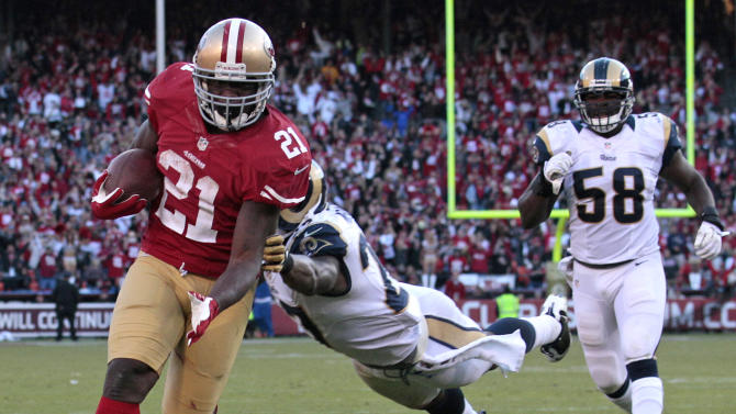 San Francisco 49ers running back Frank Gore carries the ball on a 21-yard touchdown run past St. Louis Rams free safety Quintin Mikell, center and St. Louis Rams outside linebacker Jo-Lonn Dunbar (58) during the fourth quarter of an NFL football game in San Francisco, Sunday, Nov. 11, 2012. (AP Photo/Jeff Chiu)
