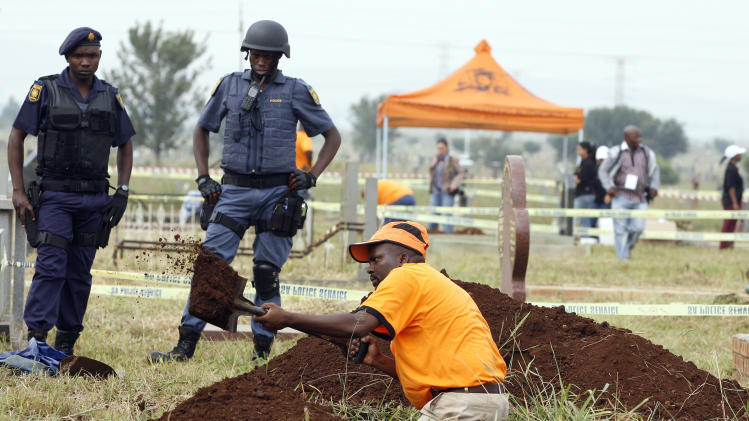 National Prosecuting Authority worker digs up a grave for exhumation of two bodies, that are believed  be those of young activists as police officer watch at Avalon Cemetery in Johannesburg, South Africa, on Tuesday, March 12, 2013. Forensic scientists on Tuesday exhumed two bodies believed to belong to young activists last seen 24 years ago at the home of Winnie Madikizela-Mandela, a discovery that has forced a new police murder investigation.   (AP Photo/Themba Hadebe)