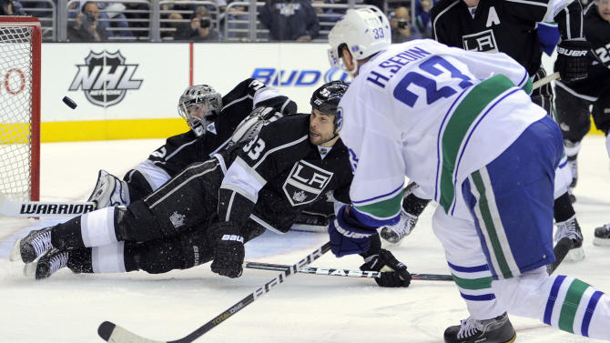 Vancouver Canucks center Henrik Sedin, right, of Sweden scores a goal on Los Angeles Kings goalie Jonathan Quick, left, as defenseman Willie Mitchell defends during the third period of Game 4 in a first-round NHL Stanley Cup playoff series, Wednesday, April 18, 2012, in Los Angeles. (AP Photo/Mark J. Terrill)