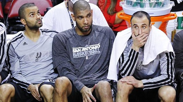 San Antonio Spurs' Tony Parker (L), Tim Duncan (C), and Manu Ginobili sit on the bench during their loss to the Miami Heat in Game 2 of their NBA Finals basketball playoff in Miami, Florida (Reuters)