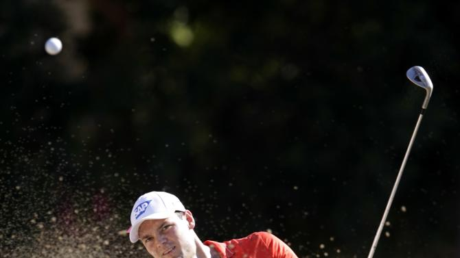 Kaymer of Germany strikes the ball from the bunker number 11 in the second round of the Dubai Desert Classic