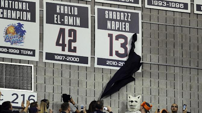 Carmen Velasquez, mother of Connecticut's Shabazz Napier, unveils her son's number on the Huskies Wall of Honor at a pep rally celebrating the the men's basketball team's NCAA championship, Tuesday, April 8, 2014, in Storrs, Conn. (AP Photo/Jessica Hill)