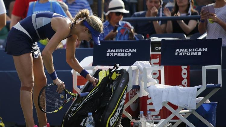 Eugenie Bouchard of Canada packs her racquet after her loss to Ekaterina Makarova of Russia at the 2014 U.S. Open tennis tournament in New York