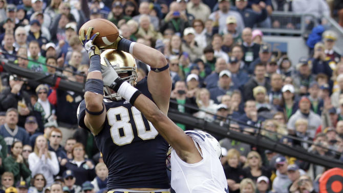 Notre Dame tight end Tyler Eifert , left, makes a catch over BYU defensive back Preston Hadley for a touchdown during the first half of an NCAA college football game in South Bend, Ind., Saturday, Oct. 20, 2012. (AP Photo/Michael Conroy)