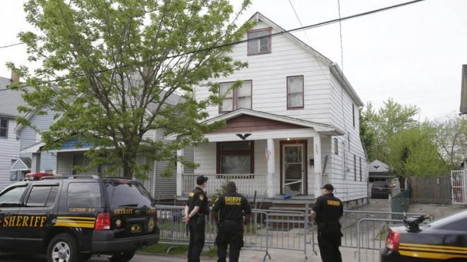 Sheriff deputies stand outside the Cleveland house where the three women were found.