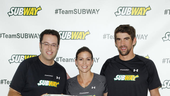 """IMAGE DISTRIBUTED FOR SUBWAY - Former Team SUBWAY marathoner Jared Fogle """"The SUBWAY Guy,"""" passes the Footlong baton to Whitney Phelps, sister of Olympic swimming champion Michael Phelps, right, as Whitney announces that she will run the ING New York City Marathon with Team SUBWAY at the Chelsea Piers Sport Center, Monday, Oct. 15, 2012 in New York. (Photo by Jason DeCrow/Invision for SUBWAY/AP Images)"""