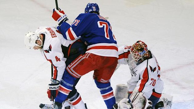 Washington Capitals' John Erskine (L) and New York Rangers' Mike Rupp (C) battle for the puck in front of Capitals' goalie Braden Holtby in 2012 (Reuters)