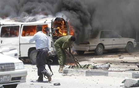 Policemen attempt to evacuate the remains of their colleagues killed at the scene of an explosion near the presidential palace in Mogadishu March 18, 2013. A car bomb exploded near the presidential palace in the Somali capital Mogadishu on Monday, killing at least 10 people in a blast that appeared to target senior government officials, police said. REUTERS/Feisal Omar