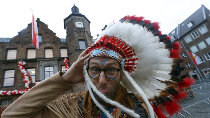 A carnival reveller holds on to his headdress during Rosenmontag in the western German city of Duesseldorf