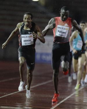 Mohamed Amman of Ethiopia, left, cuts the finish line to win the 800m men's race flanked by David Rudisha of Kenya during the international athletics meeting 'La notturna di Milano', at the Arena Civica, in Milan, Italy, Sunday, Sept. 18, 2011. (AP Photo/Luca Bruno)