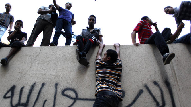 """Egyptian protesters climb the walls of the U.S. embassy with Arabic graffiti that reads """"any one but you God's prophet"""" during a protest in Cairo, Egypt, Tuesday, Sept. 11, 2012. Egyptian protesters, largely ultra conservative Islamists, have climbed the walls of the U.S. embassy in Cairo, went into the courtyard and brought down the flag, replacing it with a black flag with Islamic inscription, in protest of a film deemed offensive of Islam. (AP Photo/Nasser Nasser)"""