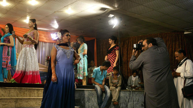 In this Sunday, Oct. 21, 2012, photo, a photographer takes pictures of Sana, 26, a Pakistani transgender, center, as others prepare for dance performance during Sana's birthday party in Rawalpindi, Pakistan. Transgender people live in a tenuous position in conservative Pakistan, where the roles of the sexes are traditionally starkly drawn. Families often push them out of the home when they're young, forcing many to prostitute themselves to earn a living. One role where they are tolerated is as dancers at weddings and other celebrations at which men and women are strictly segregated. (AP Photo/Anjum Naveed)