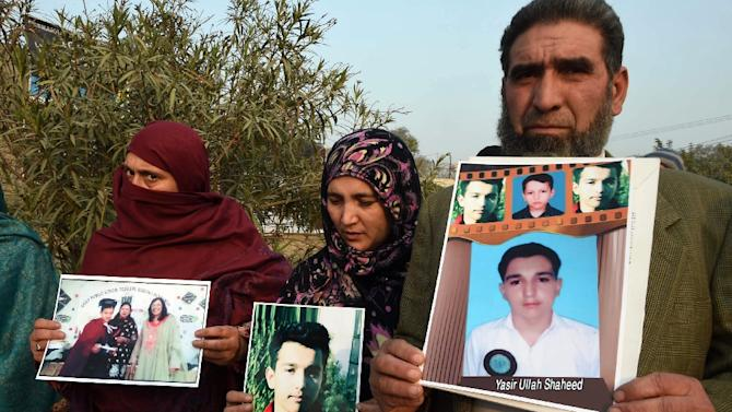 Pakistani parents display photographs of their slain children, as they gather outside an army-run school in Peshawar on December 23, 2014