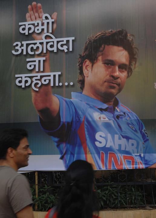 A couple look at a Sachin Tendulkar poster near Shivaji Park ground in Mumbai on Nov.16, 2013. (Photo: B L Soni/IANS)