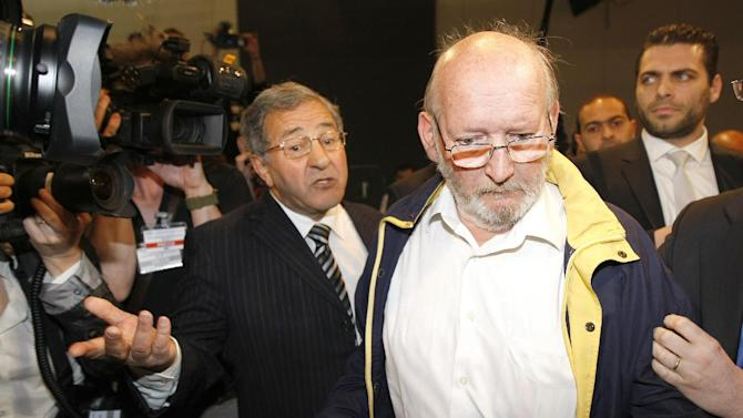 Jean-Claude Mas, who founded and ran implant-maker Poly Implant Prothese, arrives with his lawyer, Yves Haddad, left, at the Parc Chanot temporary courthouse in Marseille, southern France, for the opening of his trial, Wednesday, April 17, 2013.  Hundreds of women who received faulty breast implants are gathering in the south of France to witness the fraud trial of five executives accused of using cheap industrial silicone to fill tens of thousands of implants around the world.  The now-defunct company exported to more than 60 countries and was one of the world's leading implant makers.(AP Photo/Claude Paris)