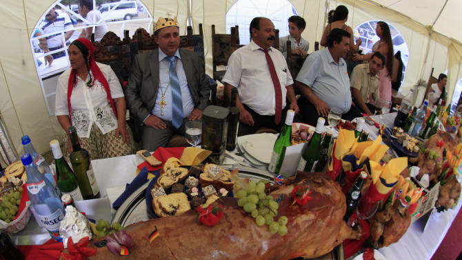 Self proclaimed international king of gypsies Stanescu sits among relatives at a table with a roasted pig on display during the traditional ethnic Roma festival in Costesti
