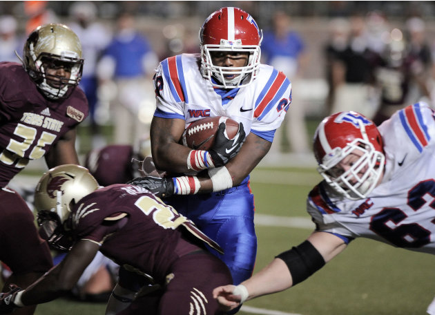 Louisiana Tech's Kenneth Dixon, center, evades Texas State's Tylond Robertson, left, and Phillip Benning behind teammate Stephen Warner, right, during the second half of an NCAA college footba