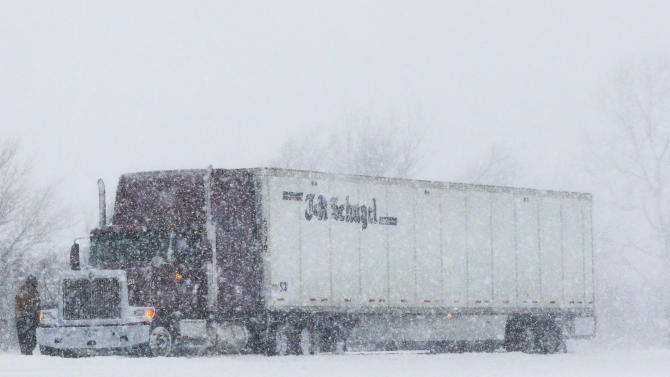 A trucker stops in almost whiteout conditions along K-10 highway near Eudora, Kan., Thursday, Feb. 21, 2013.  The Kansas Turnpike Authority encouraged drivers to stay off the turnpike entirely; it runs from Oklahoma to Kansas City. There was virtually zero visibility on the turnpike early Thursday. And I-70 and other major highways in Kansas were snowpacked and icy, according to the Kansas Department of Transportation. Kansas Gov. Sam Brownback closed executive offices, except for essential personnel. He urged residents to have an extra cup of coffee, get out a board game and play with their children. (AP Photo/Orlin Wagner)