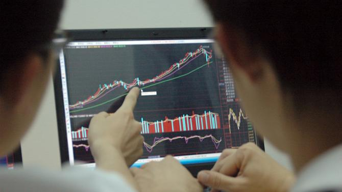 Students point at a laptop screen showing stock information, in Beijing