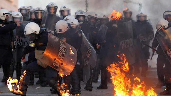 A riot police officer tries to extinguish flames from a petrol bomb thrown by protestors outside the Greek Parliament, Athens, Sunday, Feb. 12, 2012. Tens of thousands of protesters gathered in the square outside Parliament as a parliamentary debate began, with more arriving constantly. As the crowds grew, a few hundred anarchists started to throw bottles and firebombs at police, who responded with tear gas and stun grenades. (AP Photo/Thanassis Stavrakis)
