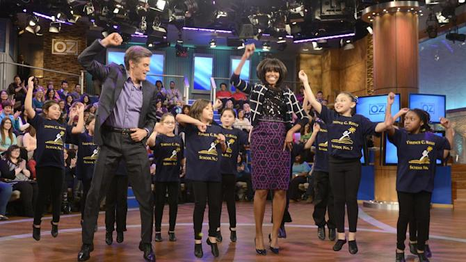 """This image released by Sony Pictures television shows first lady Michelle Obama, center, and host Dr. Mehmet Oz dancing with third graders from the Terence C. Reilly #7 School in Elizabeth, N.J. to demonstrate fun ways to keep moving in the classroom during a taping of """"The Dr. Oz Show,"""" on Friday, Feb. 22, 2013 in New York.  The school came to the attention of the White House because of their novel approach to include spontaneous dance breaks throughout the day. The episode will air on Thursday Feb. 28. (AP Photo/Sony Pictures Television, Barbara Nitke)"""