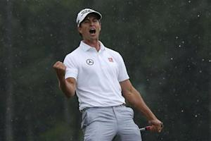 Adam Scott of Australia celebrates sinking a birdie putt on the 18th green during the final round in the 2013 Masters golf tournament in Augusta