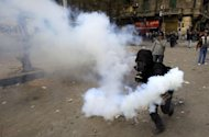 A masked Egyptian protester prepares to throw back a tear gas canister fired by security forces during clashes in downtown Cairo in February in the wake of football riots. A boy was shot dead when Egyptian forces clashed with football fans protesting against a ban on their club over the stadium riot that killed dozens last month, officials said