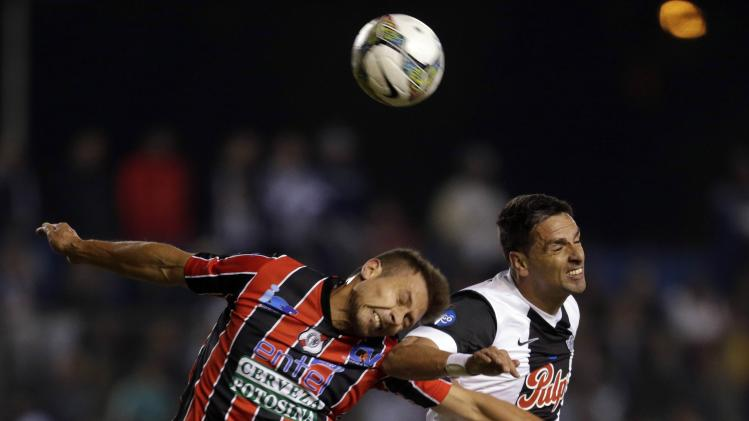 Centurion of Bolivia's Nacional Potosi battles for the ball with Lopez of Paraguay's Libertad during their Copa Sudamericana soccer match in Asuncion