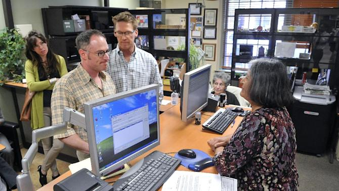 FILE - Alexander Hanna, left, and Yon Hudson are denied a marriage license by Santa Fe County Clerk Geraldine Salazar at the County Clerk's Office, in Santa Fe, N.M. on Thursday, June 6, 2013. Across the country, the June 2013 landmark Supreme Court rulings on same-sex marriage have energized activists and politicians on both sides of the debate. Efforts to impose bans - and to repeal them - took on new intensity, as did a spate of lawsuits by gays demanding the right to marry. (AP Photo/Albuquerque Journal, Eddie Moore)