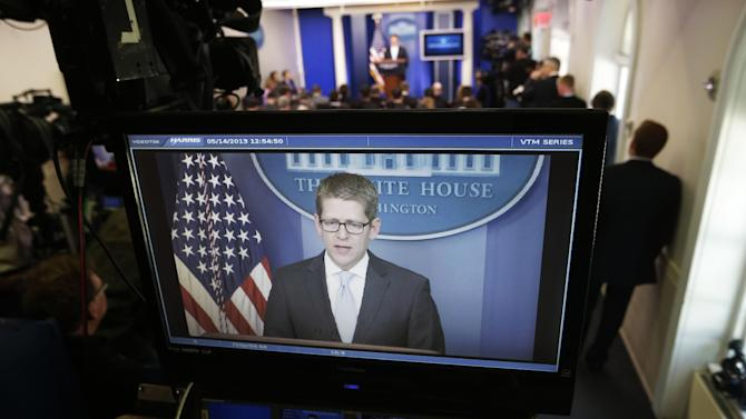 White House press secretary Jay Carney, rear, is seen on a television monitor during his daily news briefing at the White House in Washington, Tuesday, May, 14, 2013. Carney touched on various topics including the Justice Department's secretly obtaining two months of telephone records of reporters and editors for The Associated Press and IRS.  (AP Photo/Pablo Martinez Monsivais)