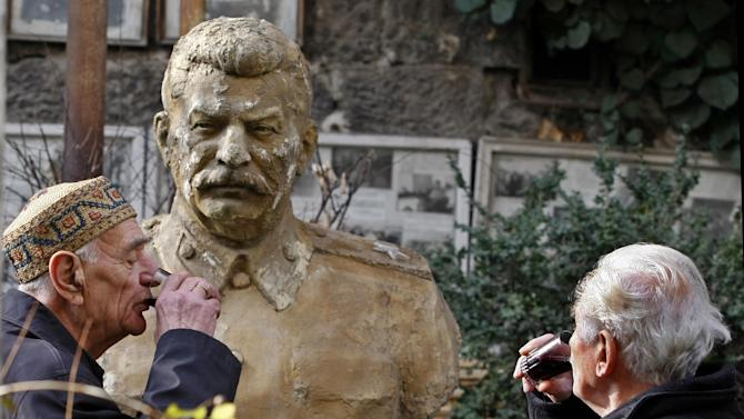 Ushangi Davitashvili, right, and his neighbor Guram Dochviri drink red wine to commemorate the 133th birthday of Soviet dictator Joseph Stalin near his bust that stands in the courtyard of Davitashvili's apartment building in the Georgian capital, Tbilisi, Friday, Dec. 21, 2012. Stalin was born in Georgia in 1879 and led the Soviet Union through decades of totalitarian reforms and political purges. (AP Photo/Shakh Aivazov)