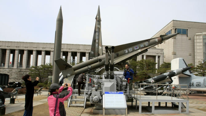 Foreign visitors take souvenir photos near a mock North Korean Scud-B missile, back left, and other South Korean missiles at the Korea War Memorial Museum in Seoul, Monday, March 19, 2012. North Korea vowed Sunday to go ahead with plans to launch a long-range rocket, rejecting criticism in the West that it would scuttle recent diplomacy. (AP Photo/Lee Jin-man)
