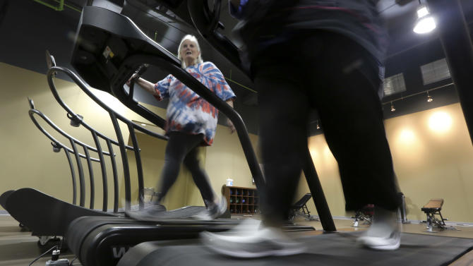 Gym members use as treadmill to warm up for a morning exercise class at Downsize Fitness Thursday, Jan. 3, 2013, in Addison, Texas.  Downsize Fitness is a selective gym where the rule is that new members must tip the scales. New members are weighed and have their body mass index measured. (AP Photo/LM Otero)