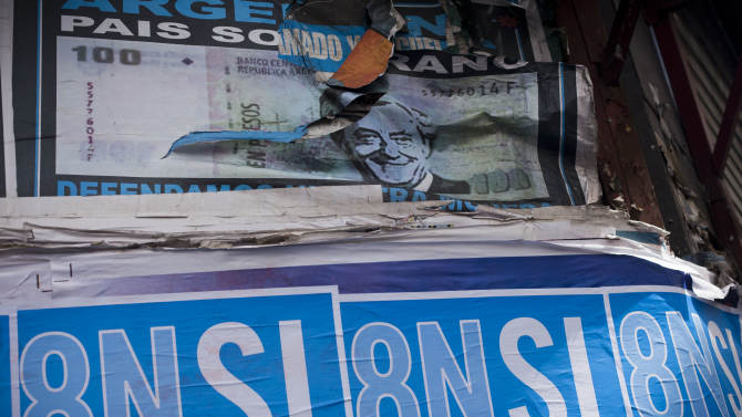 """A poster with a photo of Argentina's late President Nestor Kirchner, top, is partially covered by posters promoting an anti-government march in Buenos Aires,  Argentina,  Wednesday, Nov. 7, 2012. People are using social networks instead of political parties to mobilize a massive march for Thursday against the leadership of Argentina's President Cristina Fernandez, mobilizing what they hope will be the largest anti-government protest the country has seen in more than a decade. The poster reads in Spanish """"Yes to democracy, no to re-election."""" (AP Photo/Victor R. Caivano)"""